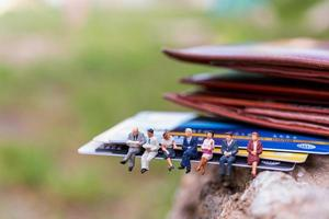 Miniature businesspeople sitting on a credit card, business and finance concepts