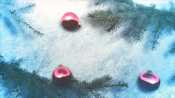 geanimeerde close-up rode ballen en groene kerstboomtakken op glanzend ijs achtergrond video