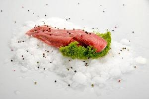 Fresh raw fish fillet steak on ice with pepper and salad on white background