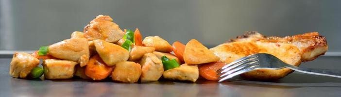 Roasted chicken seasoned slices with carrots and leeks on a stainless steel background