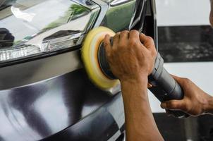 Person polishing a car headlight photo