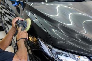 Person polishing a black car photo