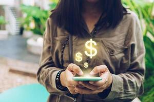 Woman uses smartphone to earn money online with dollar icon pop up photo