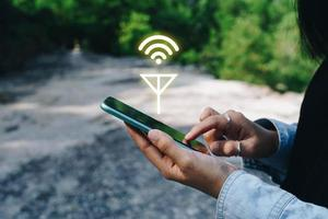 La mano de la persona con un teléfono inteligente en busca de señal wifi en el bosque foto