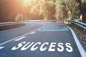 La palabra de éxito en la carretera representa el comienzo de un viaje hacia el destino. foto
