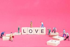Miniature workers building the word Love on wooden blocks with a pink background, Valentine's Day concept photo