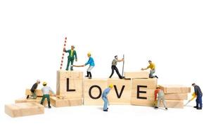 Miniature workers building the word Love on wooden blocks with a white background, Valentine's Day concept photo