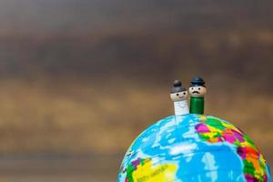 Muñecas de madera en miniatura en un globo terráqueo con un fondo de madera foto