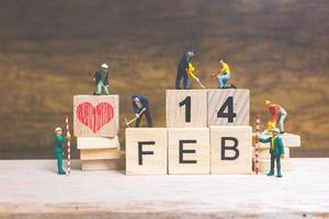 Miniature workers building the words and dates for Valentine's Day on wooden blocks with wooden background, Valentine's Day concept photo