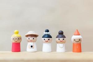 Muñecas de madera en miniatura con caras felices sobre un fondo de madera foto