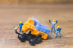 Miniature workers repairing a wheel off a truck on a wooden background photo