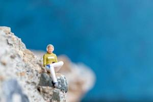 Miniature woman wearing headphones and listening to music on a smartphone sitting on the rock