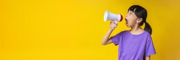 Young Asian girl in purple shirt yelling into white megaphone in studio with yellow background photo