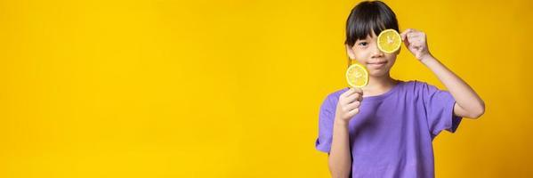 Young Asian girl in violet shirt holding lemon slices isolated in studio with yellow background photo