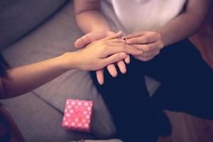 Close-up of man putting ring on woman's finger on couch with pink gift box photo
