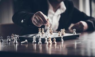 empresario jugando una partida de ajedrez, concepto de negocio foto
