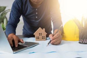 Arquitecto trabajando en un plano junto a una computadora portátil, un casco, una taza de lápices y un modelo de casa foto