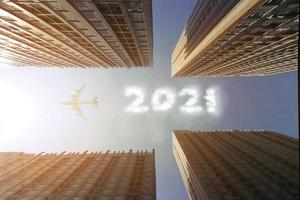 Airplane flying over skyscrapers to make a cloud text 2021 in the sky photo
