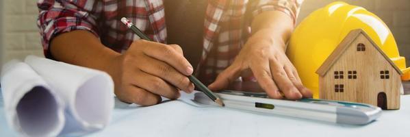 Primer plano del hombre trabajando en un plano junto al casco, modelo de casa y papeles enrollados foto