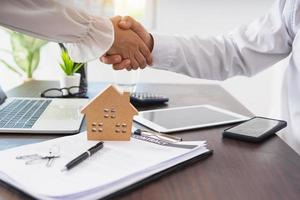 Two people shake hands next to a house model, a laptop, and a contract photo