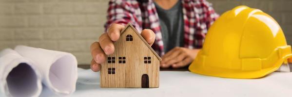Close-up de la mano del hombre sosteniendo el modelo de la casa junto al casco y papeles enrollados foto