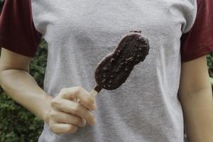 persona sosteniendo un helado en un palo