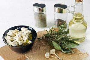 Marinated feta on a plate on a wooden board with spices on a white background photo