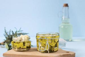 Marinated feta in a glass jar and spices against a blue background photo