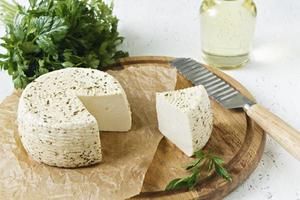 White cheese on a wooden board on a white background with greens photo