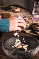 A person pouring sliced spices from a chopping board into a black bowl photo