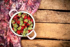 Strawberries in a bucket bowl on a wooden surface photo