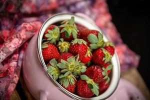 Strawberries in a bowl on a wooden table photo