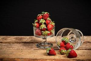 Strawberries in a glass on a wooden table photo