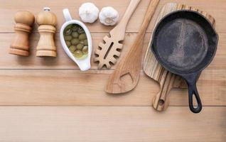 Skillet with wooden utensils and fresh ingredients