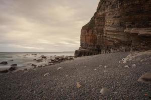 playa con montañas al fondo y cálida luz del atardecer foto