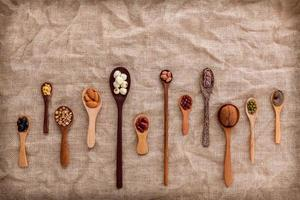 Beans and lentils in wooden spoons photo