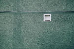 una ventana en la fachada verde del edificio foto