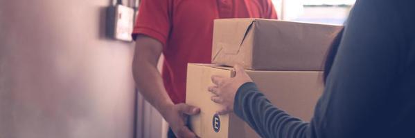 Repartidor sosteniendo la entrega de cajas o paquetes envueltos a una persona.