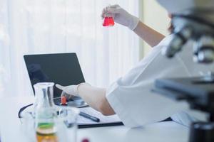 Científico de laboratorio sosteniendo un vaso de precipitados con líquido rojo y trabajando en un portátil