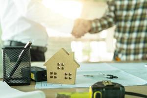 dos personas dándose la mano junto al plano y la casa modelo foto