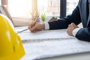 Arquitecto trabajando en planos en Office foto