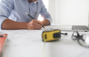 Man working on a blueprint next to laptop and tape measure photo