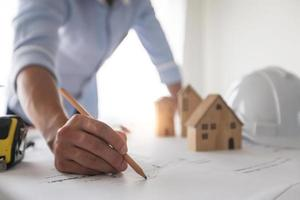 Man working on a blueprint next to model houses, hard hat, and tape measure photo
