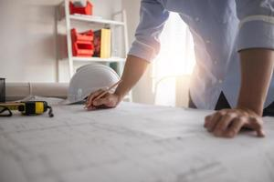 Businessman working on blueprint next to tape measure, hard hat, and window photo