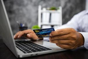 primer plano, mano, de, hombre, tenencia, tarjeta de crédito, y, trabajando, en, computadora portátil foto