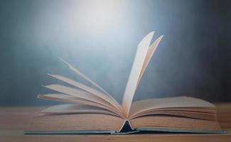 Open book on wooden table with blue background photo
