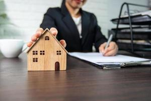 Businesswoman holding a model house and signing a contract photo