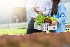 Man holding tablet next to woman holding crate of vegetables in a greenhouse photo