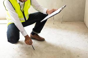 Hombre en chaleco de construcción amarillo sosteniendo el portapapeles e inspeccionando el piso foto
