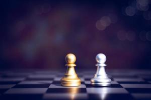 Piezas de ajedrez de peón de oro y plata en tablero de ajedrez foto